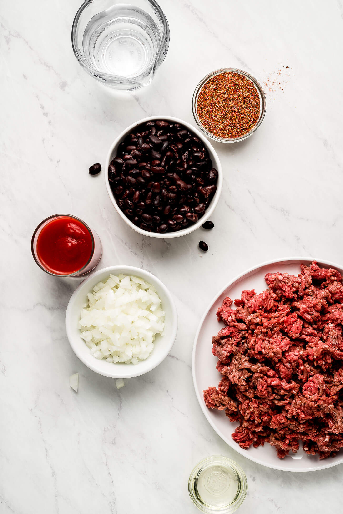 Ingredients on a marble surface: water, taco seasoning, black beans, tomato sauce, onions, oil, and ground beef.