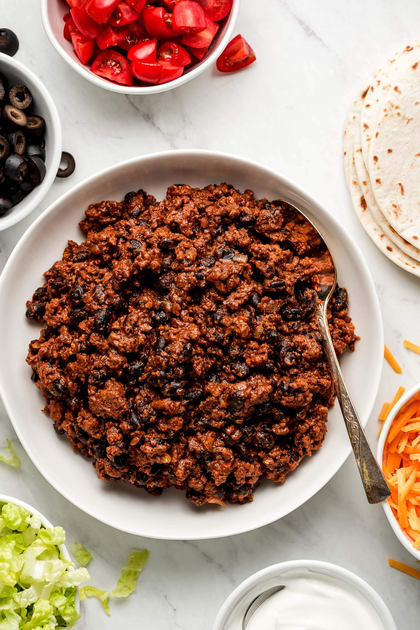 Ground Beef Taco Meat with beans in a white serving bowl with bowls of condiments to the sides.