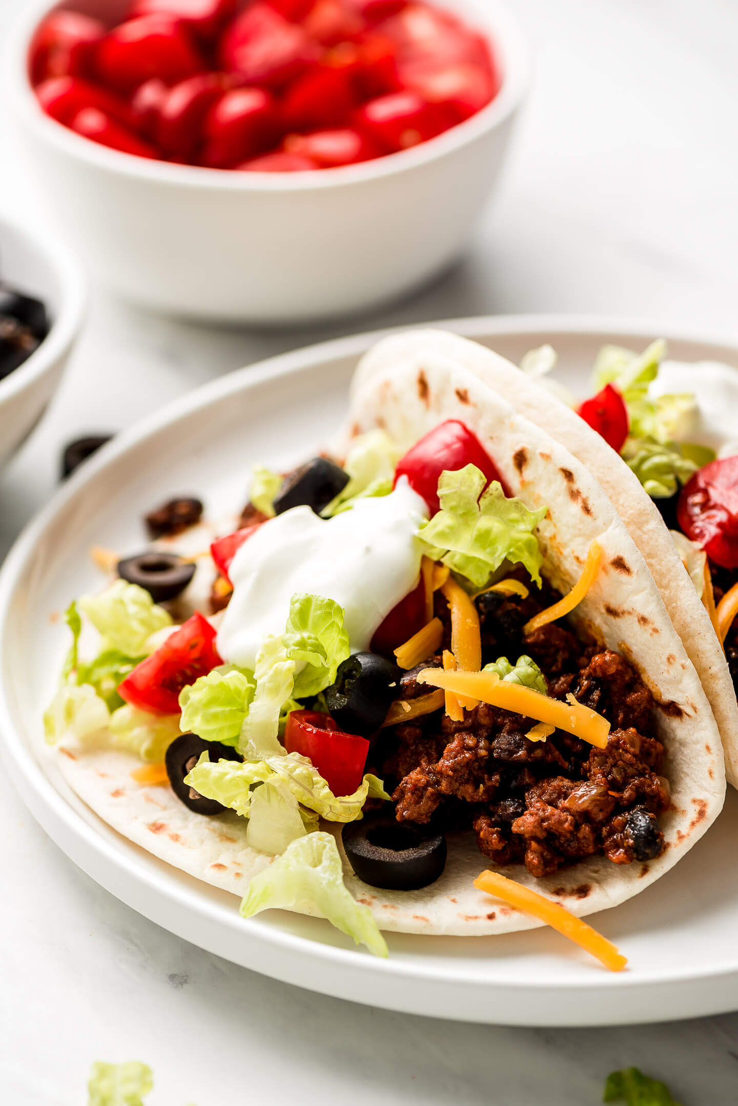 Soft shell Ground Beef Tacos filled with ground beef, beans, cheese, lettuce, olives, tomatoes, and sour cream.