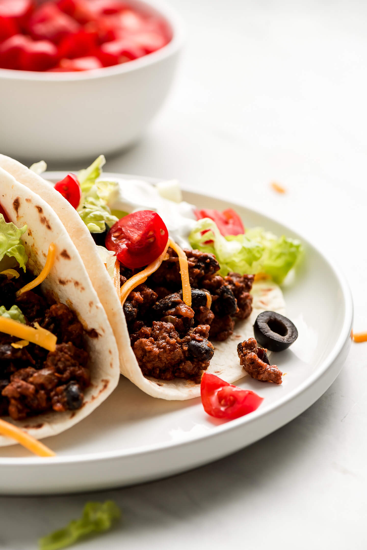 A tortilla filled with ground beef filling and topped with lettuce, tomatoes, cheese, and sour cream.
