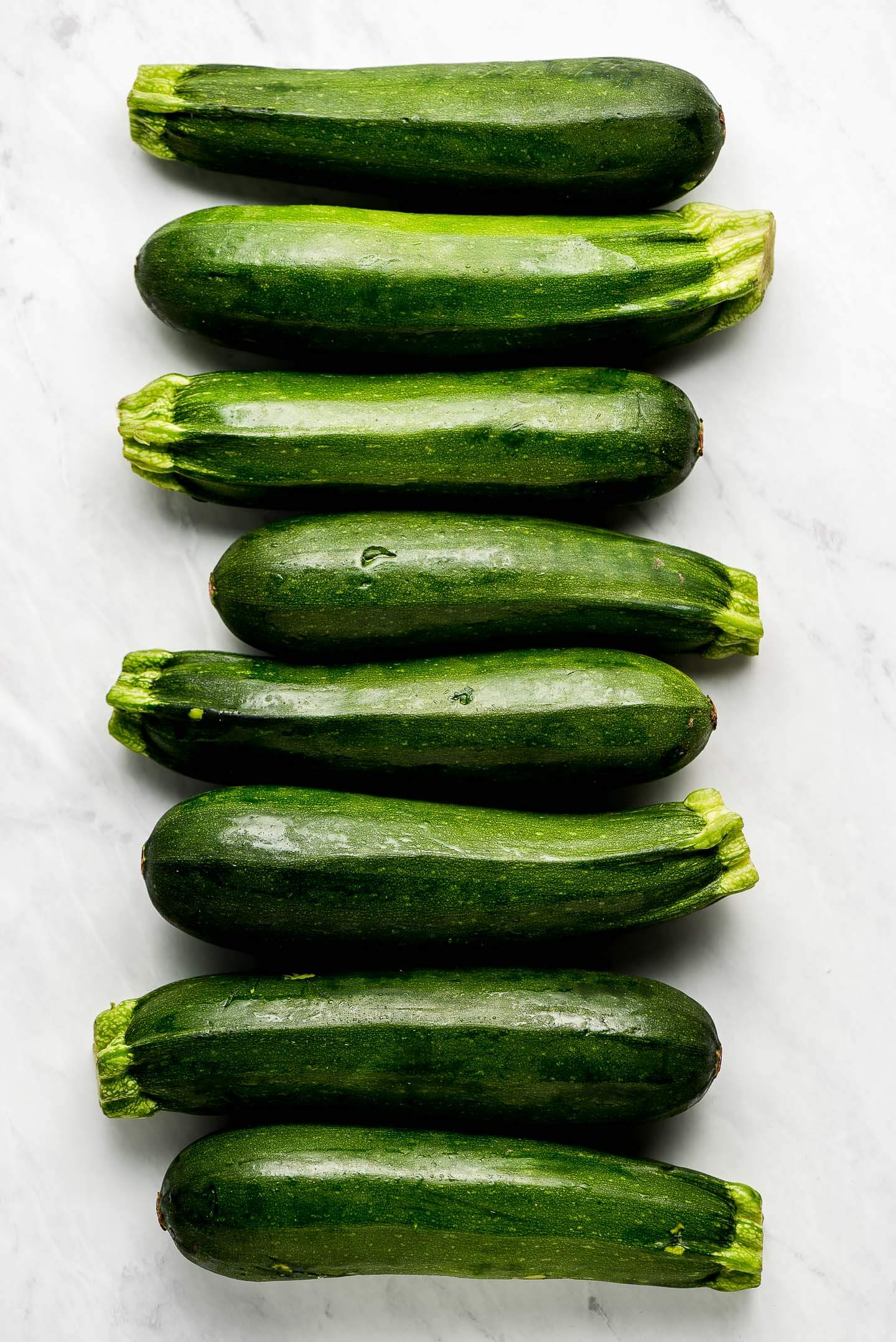 Multiple zucchini lined up on a marble surface.