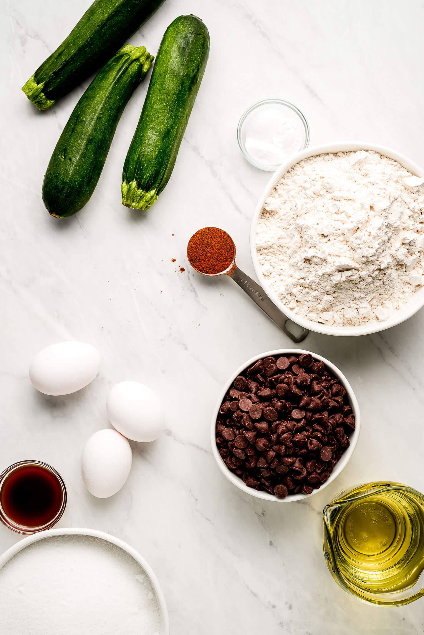 Ingredients on a marble surface: zucchini, flour, cinnamon, baking soda, chocolate chips, oil, eggs, sugar, and vanilla extract.