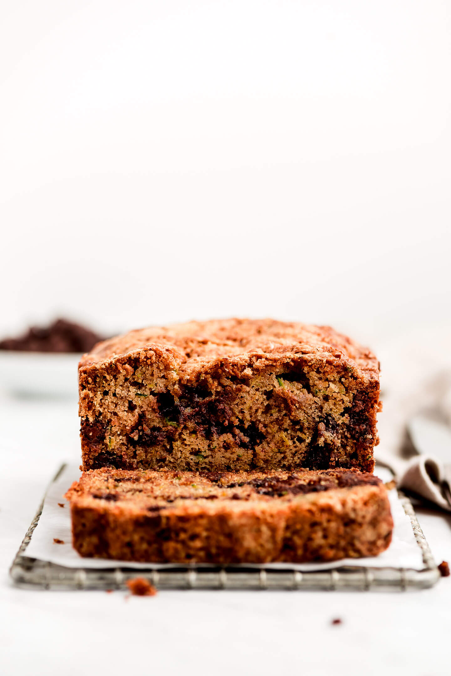 Chocolate Chip Zucchini Bread on a cooling rack with a slice cut off and laying in front.