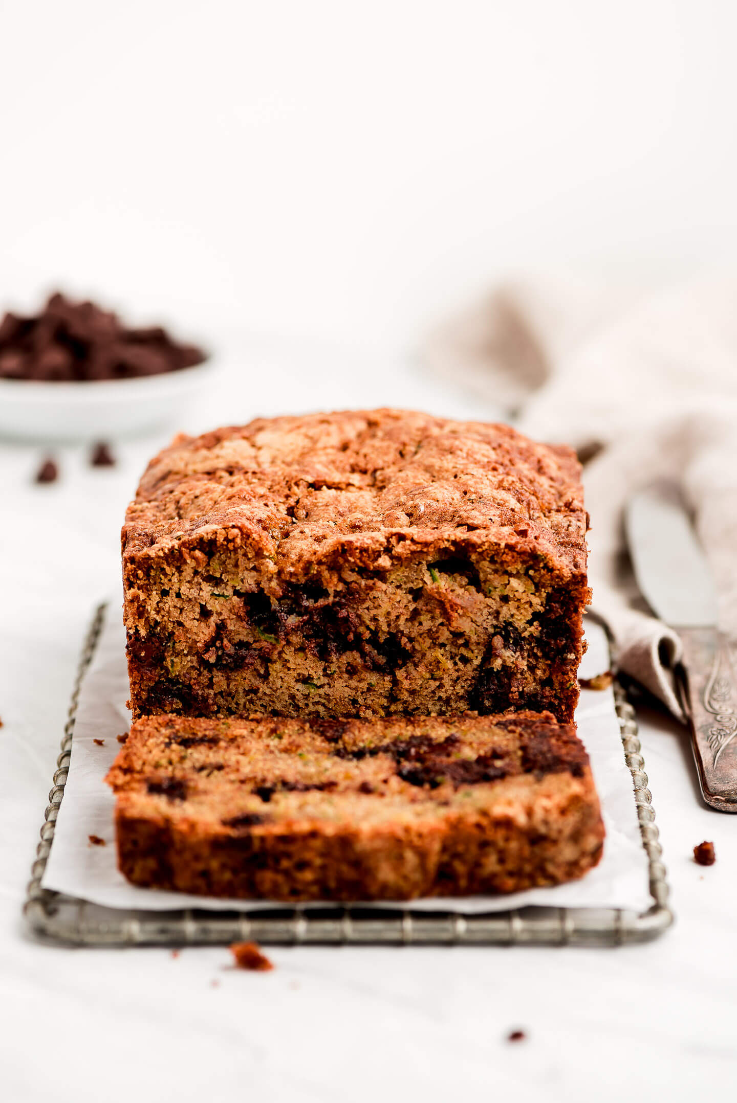 A loaf of zucchini bread on a small cooling rack with chocolate chips in the background.