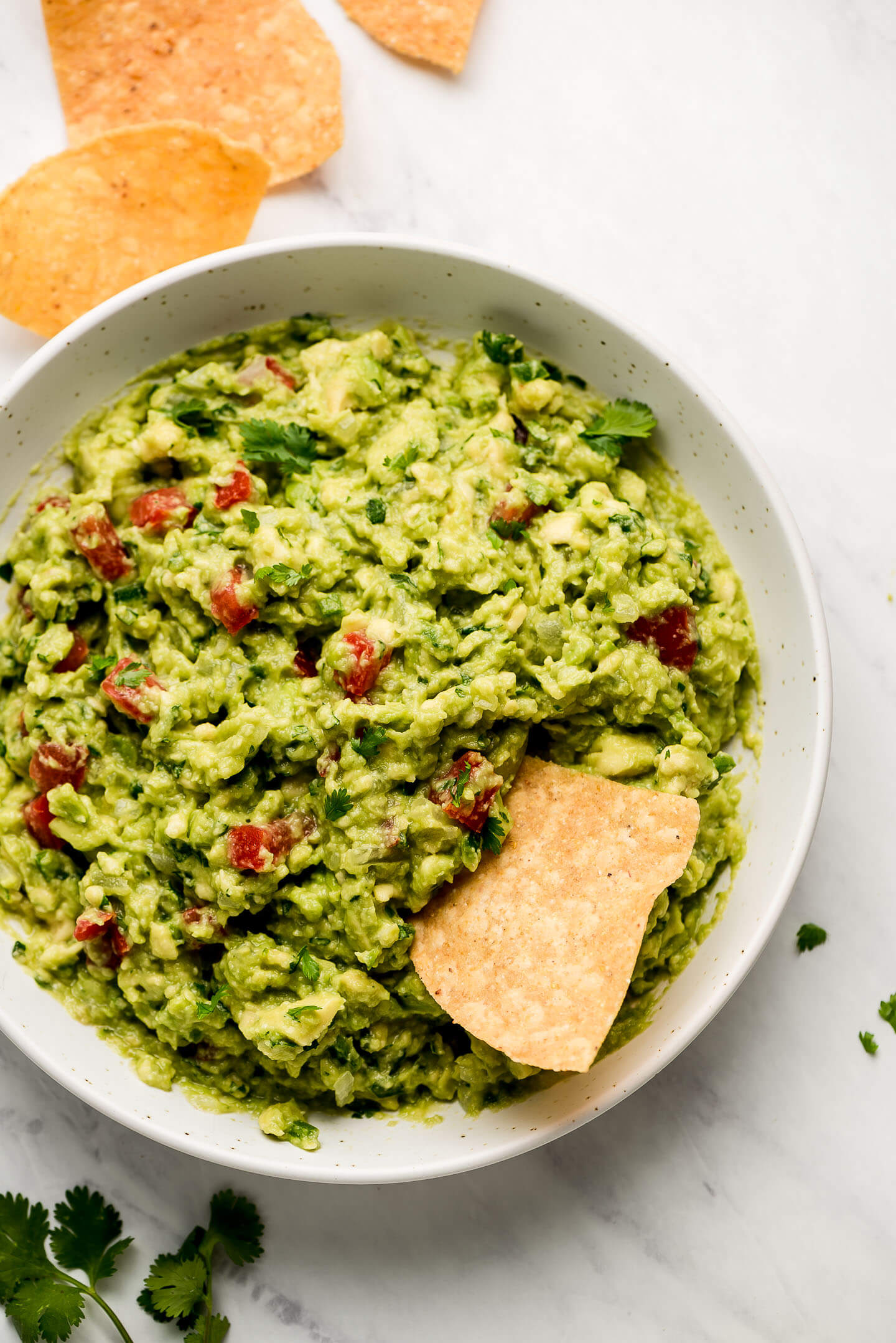 Top view of a large bowl of Homemade Guacamole with a chip in the side.