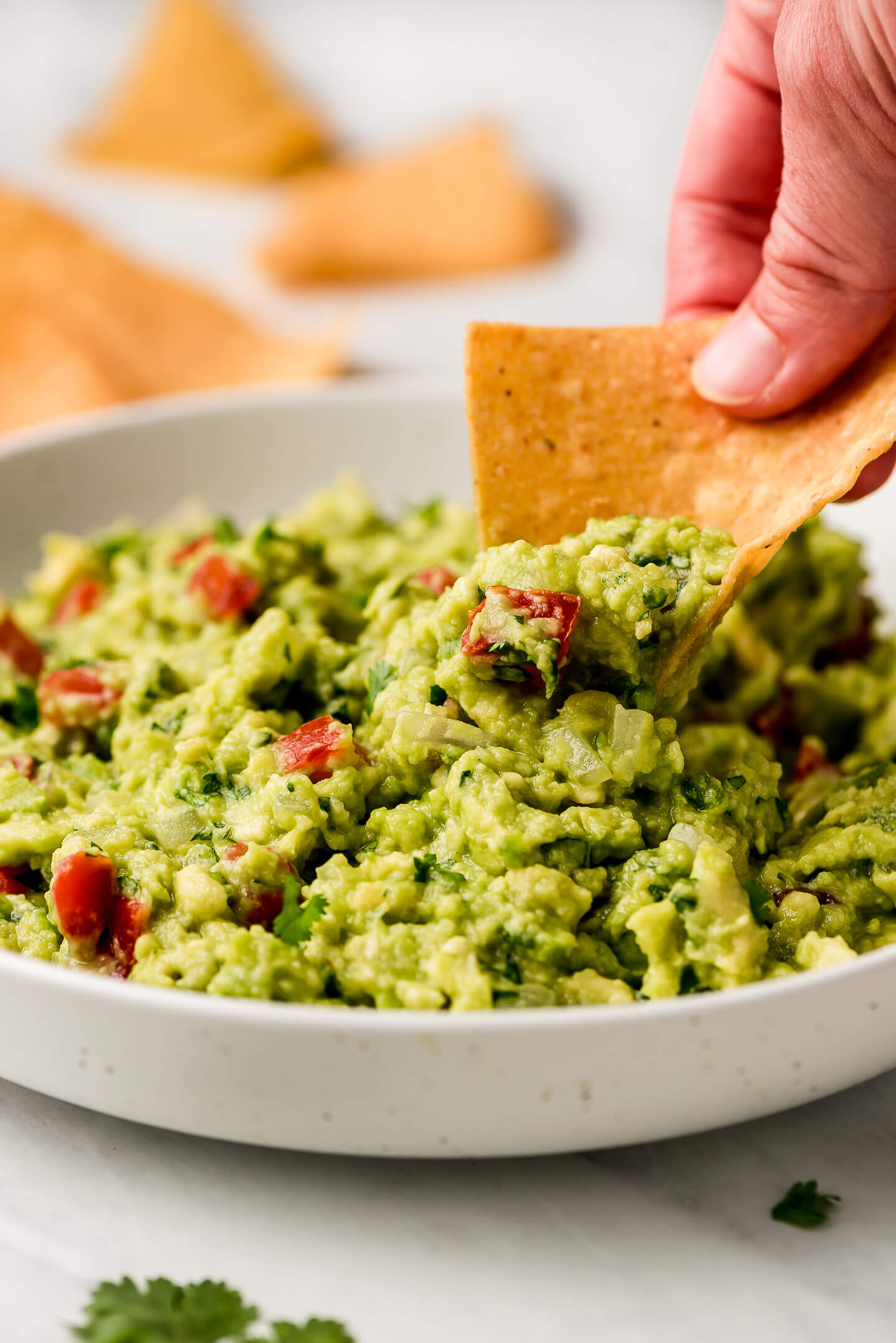 A hand scooping out guacamole with a tortilla chip.