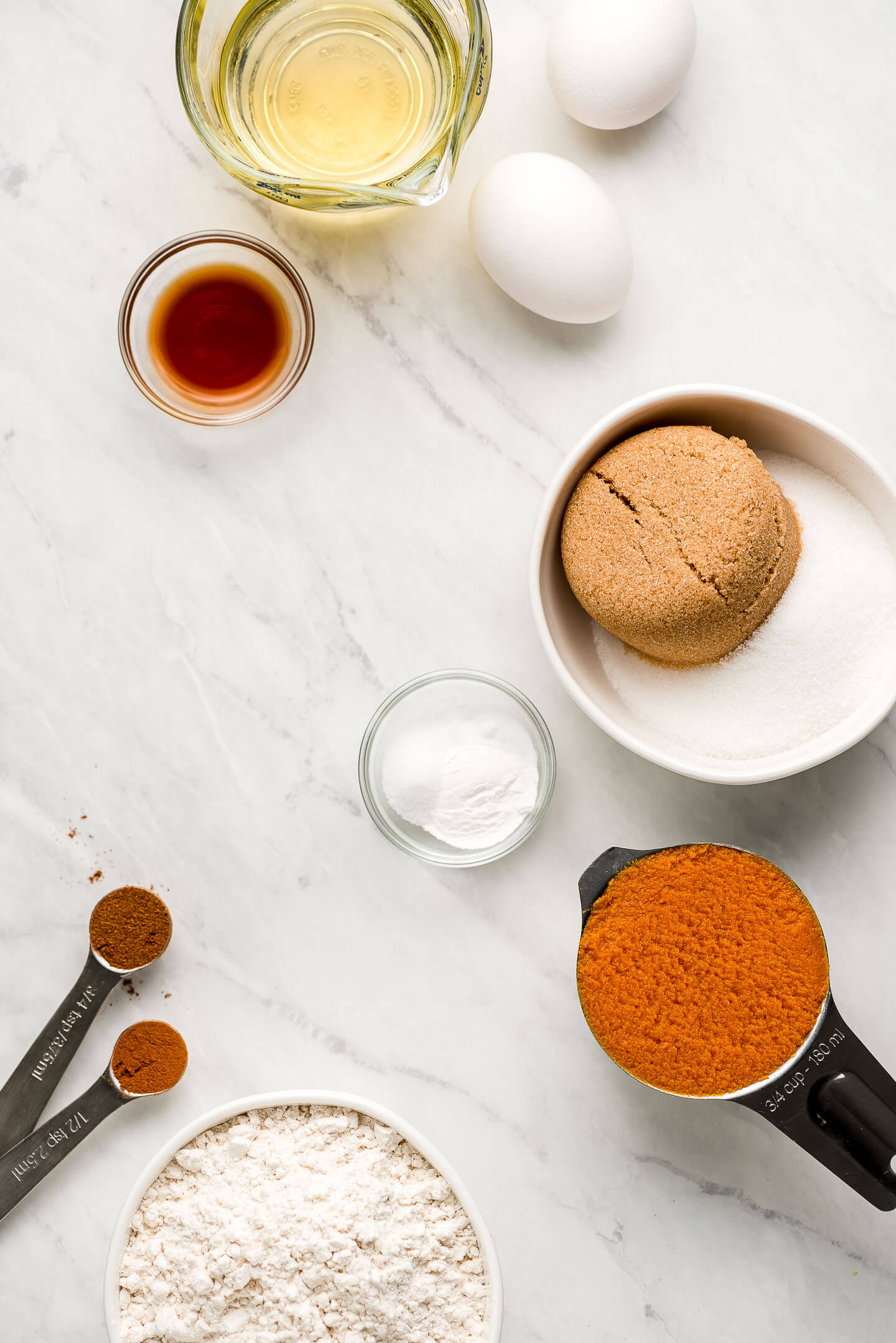 Ingredients on a marble surface- oil, eggs, vanilla extract, brown and granulated sugar, baking soda, pumpkin puree, flour, and warm spices.