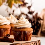 A Pumpkin Cupcake topped with cinnamon Cream Cheese Frosting on a wood slice cake stand.