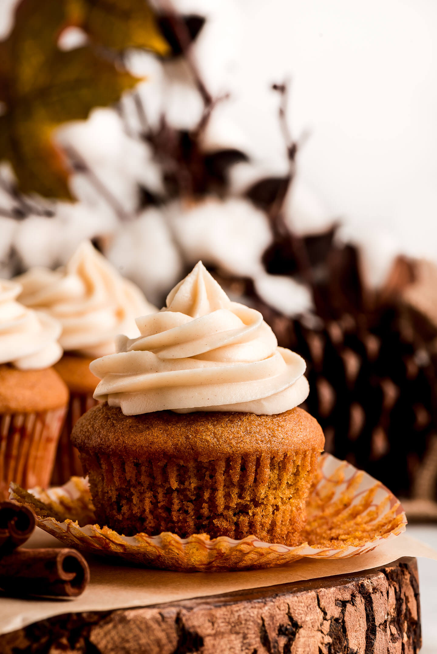 A Pumpkin Cupcake topped with cinnamon Cream Cheese Frosting with the wrapper peeled down.