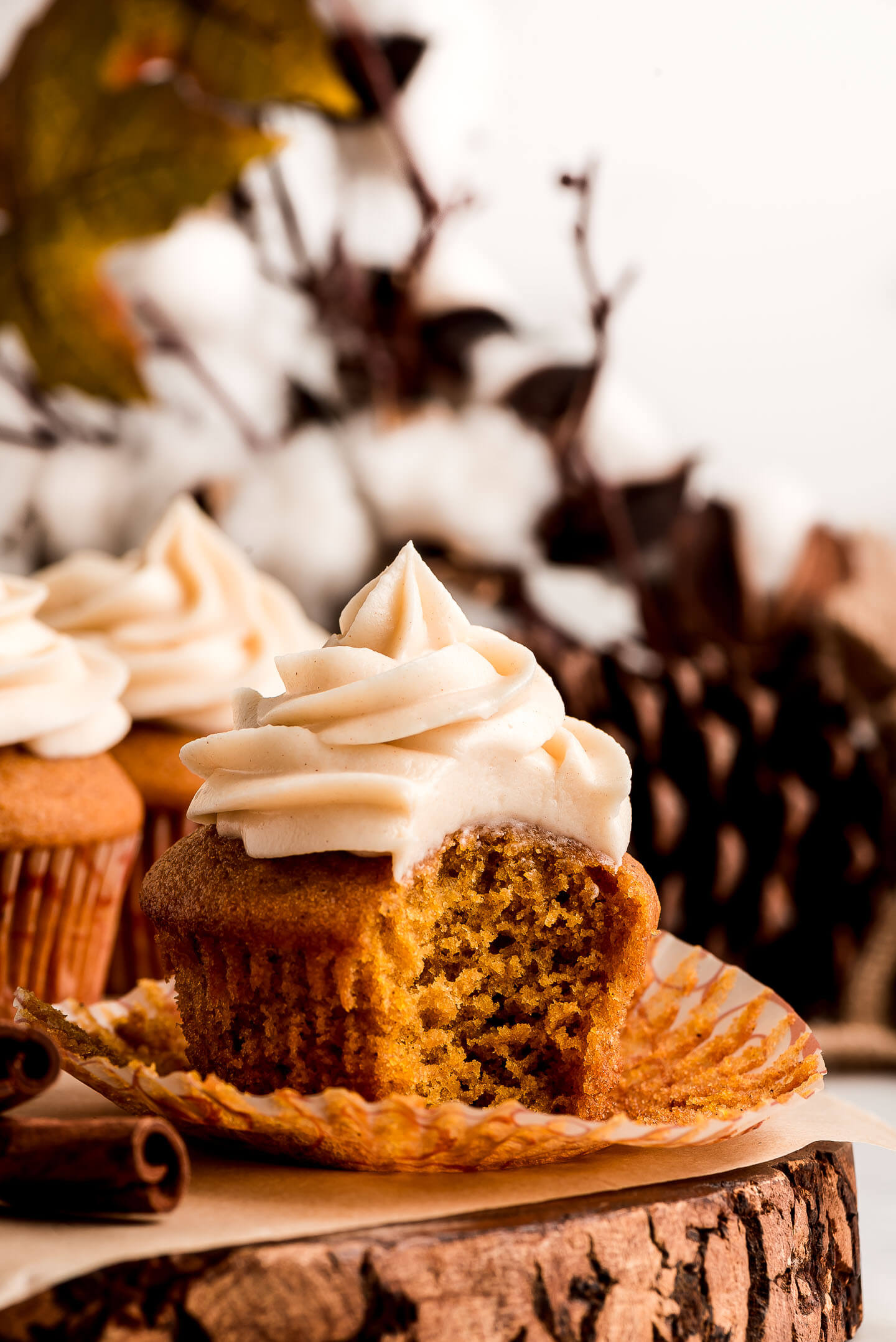 A Pumpkin Cupcake topped with cinnamon Cream Cheese Frosting with a bite taken out.