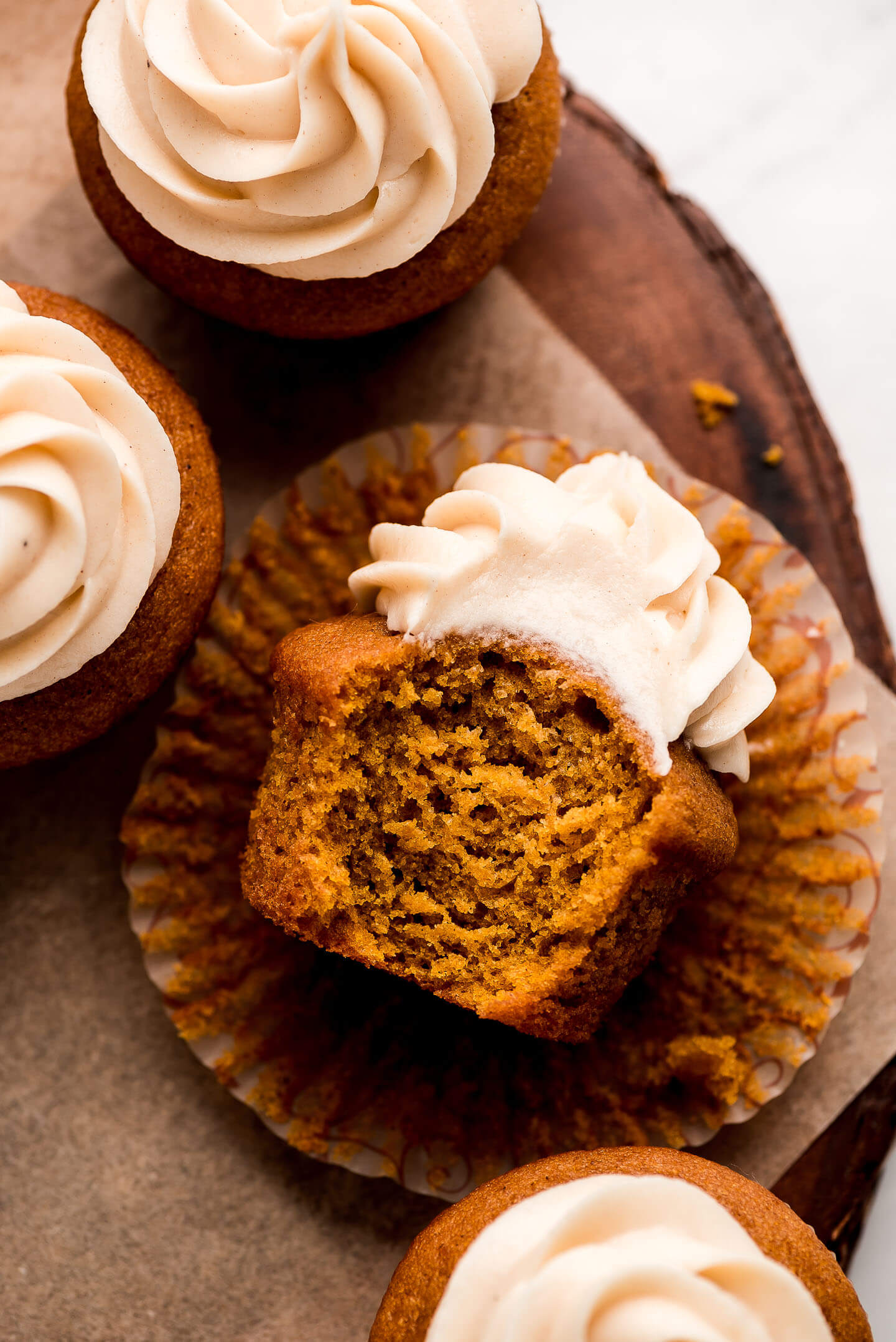 A Pumpkin Cupcake on its side with a bite taken out, focusing on the fluffy crumb interior.