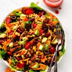 Taco Salad dizzled with Catalina dressing and a jar of it to the side.